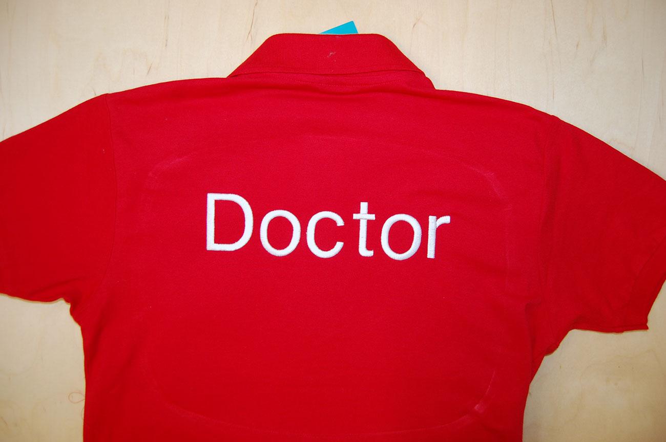 Wyhaftowany napis na plecach czerwonej koszulki polo