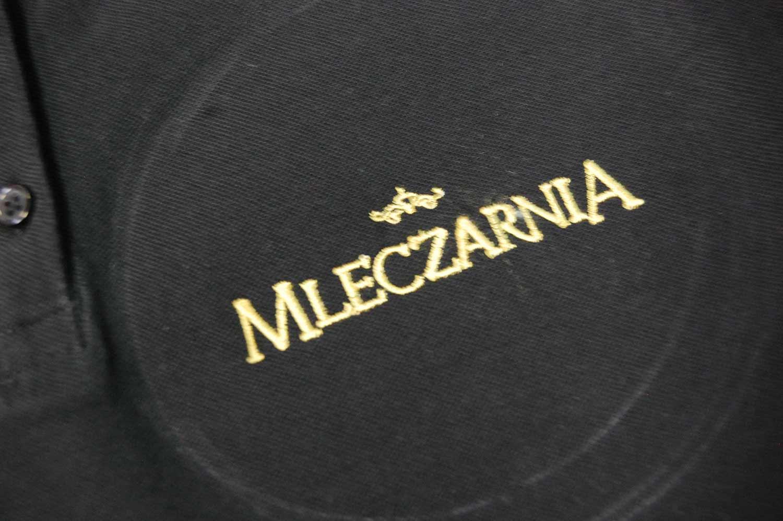 Haft żółtą nicią napisu Mleczarnia.