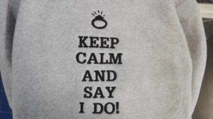 Wyhaftowany napis na szarej bluzie: Keep calm and say i do!