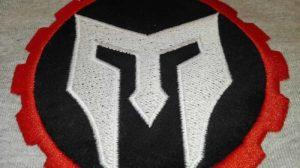 Wyhaftowane-logo-spartanina-na-szarej-tkaninie